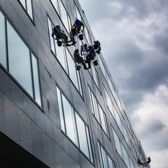 Climbers washing windows of a modern high-rise building