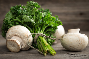 Fresh parsley with white mushrooms. On wooden background