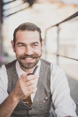 handsome big moustache hipster man smoking pipe