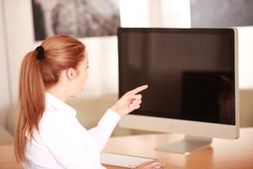 Frau zeigt auf Bildschirm