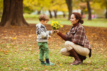 Cute little boy giving flowers to his mother