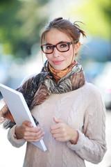 Junge Frau mit Mappe draußen