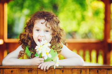 Laughing girl with a flower in her hand. Toning photo.