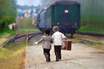 Two boys, dressed in vintage clothing and hat, with suitcase