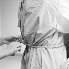 Surgeon assistant tying surgical attire