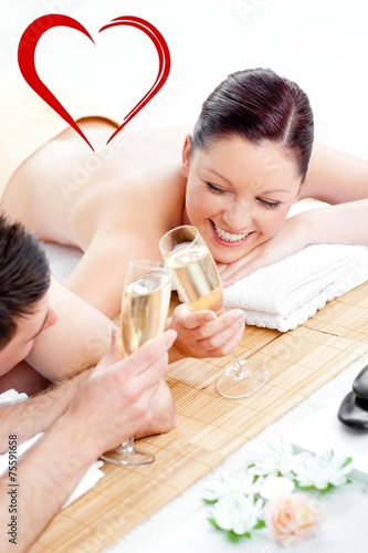 Loving young couple drinking champagne lying on a massage table - 75591658