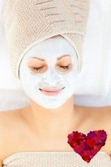 Cute young woman with closed eyes having white cream