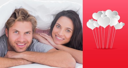 Composite image of beautiful couple smiling under the cover