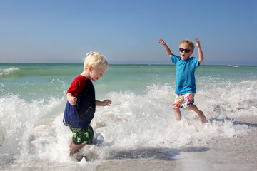 Two Young Children Playing and Splashing in Ocean Water