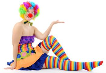 Clown sitzt und präsentiert