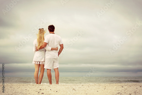 A happy couple isstanding on beach at morning, vintage color - 75594490