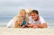Portrait Of Happy Family of Four People Relaxing on the Beach