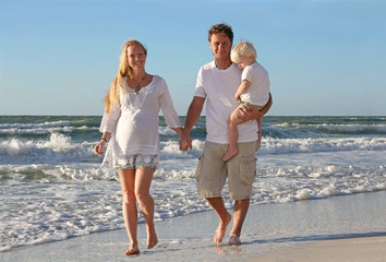 Happy Family of Three People Walking on Beach Along Ocean
