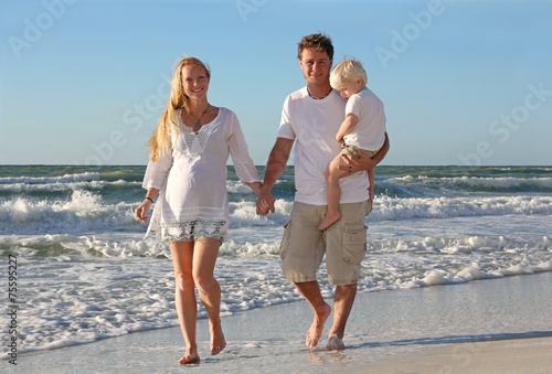 Happy Family of Three People Walking on Beach Along Ocean