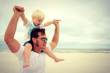 A happy child is riding on his fathers back on the beach