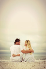 Happy Couple Sitting on Beach by Ocean in Vintage Color