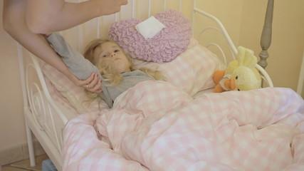 Little girl sick in bed drinks milk