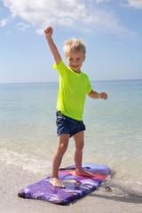 Happy Child Standing on Boogie Board in Ocean