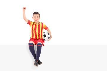 Junior soccer player gesturing joy seated on panel