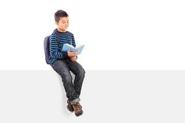 Schoolboy reading a book seated on signboard