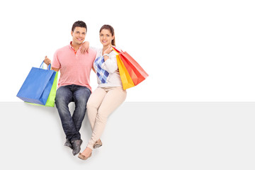 Young husband and wife holding shopping bags