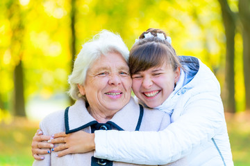 granddaughter and grandmother embracing in autumn park