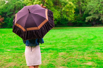 woman standing in the meadow under the open umbrella