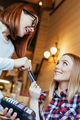 Young Woman Paying A Bill By Credit Card