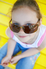 Adorable cute pretty little gir in sunglasses playing outdoors