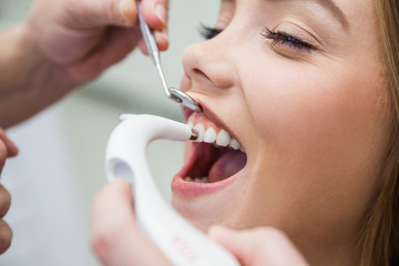 Female Patient Treated With Dental Equipment