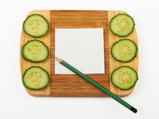 Cucumber and notepad on wooden cutting board.
