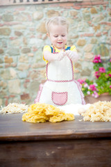 Girl preparing pasta dough on wooden table.