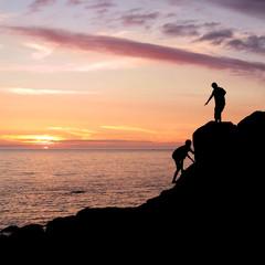 Climbing silhouettes at rocky seashore