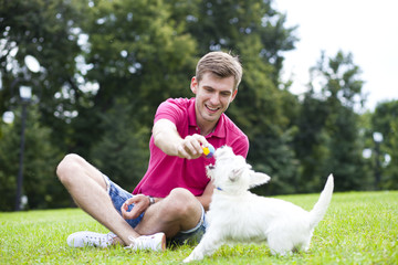 Young man playing with his dog in the park