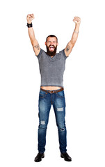 Excited handsome Tattooed bearded man with arms raised in succes
