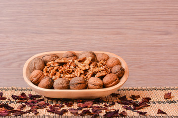Walnuts on wooden bowl with dried rose petals on table