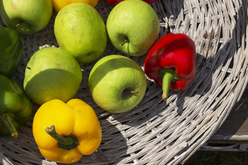 apples and peppers in a wicker basket
