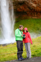 Tourists with SLR camera by waterfall on Iceland
