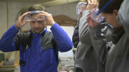 Trainer with students in workshop putting security glasses on