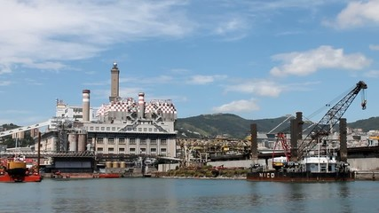 Old lantern of Genoa and harbor industrial cranes.