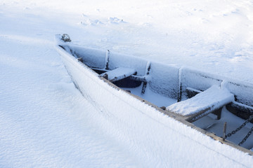 Boat under snow on the shore