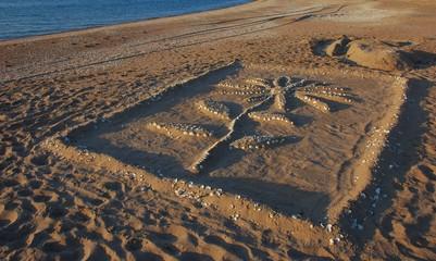 Скульптура цветок из песка и ракушек на пляже