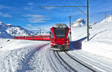 A red swiss train running through the snow