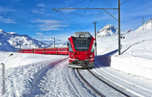 Leinwanddruck Bild A red swiss train running through the snow
