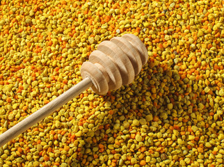 Wooden honey dipper over bee pollen