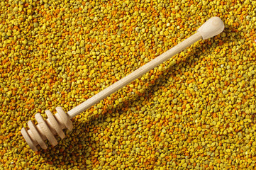 Wooden honey dipper on bee pollen granules surface