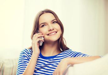 smiling teenage girl with smartphone at home