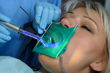 dentist with patient, using dental curing light