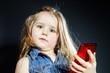 Cute little girl speaks using new cell phone.