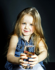 Cute little girl with long hair holding glass of water